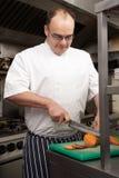 Chef-kok die Groenten in de Keuken van het Restaurant voorbereidt stock fotografie