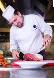 Chef-kok die groot stuk van vlees snijden royalty-vrije stock foto's