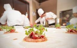 Chef-kok die haar plaat beëindigen en klaar om bij de lijst te dienen Finall Royalty-vrije Stock Foto