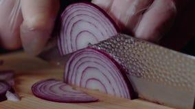 Chef-kok die hamburger maken De mens snijdt de ui Snel knipsel van groenten Halve ringen van uien boog voor het braden De handen stock footage