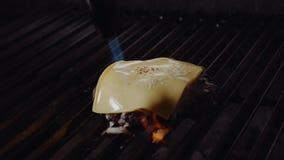 Chef-kok die hamburger maken De kok smelt kaas op een hamburger De kok gebruikt een soldeerlamp om kaas op een vleeskotelet te sm stock footage