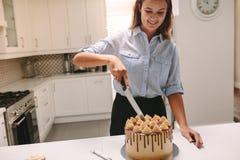 Chef-kok die heerlijke cake snijden stock foto