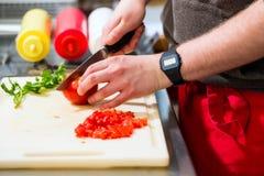 Chef-kok die hotdog in snel voedselsnackbar maken royalty-vrije stock fotografie