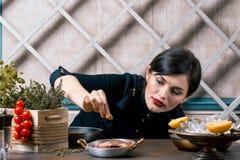 Chef-kok die kruiden op schotel in commerciële keuken bestrooien Gastronomisch restaurant royalty-vrije stock fotografie