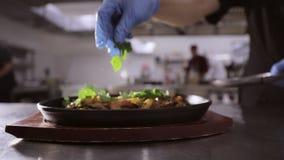 Chef-kok die kruiden toevoegen aan pan met groenten en vlees op houten tribune stock footage