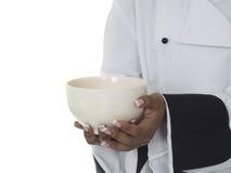 Chef-kok die lege kom dient stock afbeelding