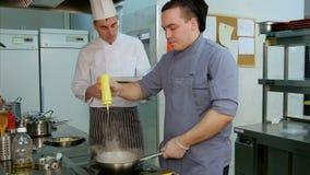 Chef-kok die met kookboek kokstagiair opdragen hoe te om garnalen te braden stock footage