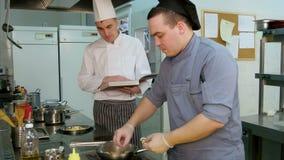 Chef-kok die met receptenboek op jonge kok letten voorbereidend schotel in de keuken stock footage