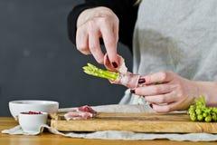 Chef-kok die miniasperge kookt Zijaanzicht, keukenachtergrond, concept het koken van asperge in bacon stock foto