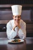 Chef-kok die op de teller met een schotel leunen Royalty-vrije Stock Fotografie