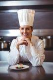Chef-kok die op de teller met een schotel leunen Royalty-vrije Stock Afbeeldingen