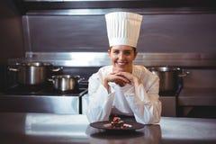 Chef-kok die op de teller met een schotel leunen Royalty-vrije Stock Foto's