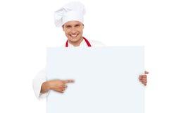 Chef-kok die op het lege witte aanplakbord richt royalty-vrije stock afbeelding