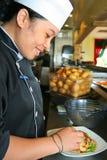 Chef-kok die op het werk glimlacht Stock Afbeelding