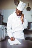 Chef-kok die op klembord schrijven terwijl het spreken op telefoon Royalty-vrije Stock Fotografie
