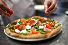 Chef-kok die pizza maakt bij keuken Stock Afbeeldingen