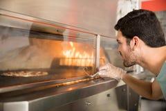 Chef-kok die pizzabaksel bekijken in moderne oven stock fotografie