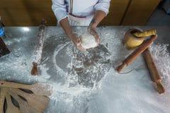 Chef-kok die pizzadeeg maken stock afbeelding