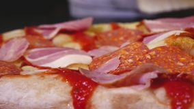 Chef-kok die plakken van ham op pizza zetten Kader Close-up die sappige heerlijke Italiaanse pizza met ham en salami koken Chef-k stock videobeelden
