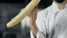 Chef-kok die pret met Frans brood hebben bij keuken De handenspel van de close-upmens met brood stock video