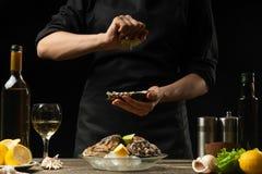 Chef-kok die ruwe oester met citroensap op de achtergrond van droge wijn op een donkere achtergrond gieten, menu, restaurant, Ita stock fotografie