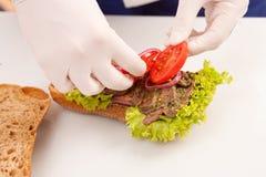 Chef-kok die sandwiches maken royalty-vrije stock foto