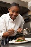 Chef-kok die Saus toevoegt aan Schotel in Restaurant stock afbeelding