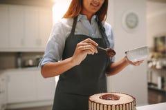 Chef-kok die smakelijke chocoladecake voorbereiden stock foto