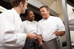Chef-kok die Stagiairs in de Keuken van het Restaurant instrueert stock afbeeldingen
