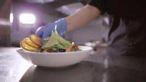 Chef-kok die toosts aan verse salade met sla, garnalen toevoegen en cheeze stock videobeelden