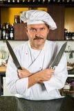 Chef-kok die twee messen houdt royalty-vrije stock afbeeldingen
