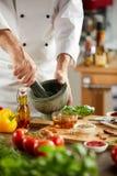 Chef-kok die verse kruiden in een stamper en een mortier malen royalty-vrije stock foto