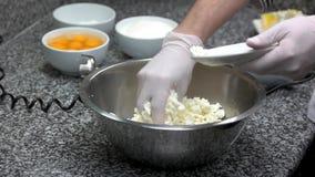 Chef-kok die vlug kaas en dooier in kom toevoegen stock videobeelden