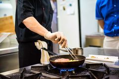 Chef-kok die voedsel op fornuis voorbereiden stock foto's