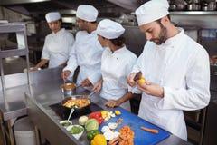 Chef-kok die voedsel van lepel in keuken controleren bij restaurant royalty-vrije stock afbeeldingen