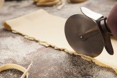 Chef-kok die wielsnijder in voorbereiding van deegwaren met behulp van stock afbeelding
