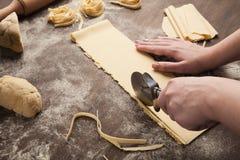 Chef-kok die wielsnijder in voorbereiding van deegwaren met behulp van stock afbeeldingen