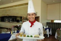 Chef-kok die zich bij restaurant bevindt stock afbeeldingen