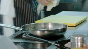 Chef-kok die zijn werkplaats schoonmaken terwijl schotel die op het fornuis worden gekookt stock footage