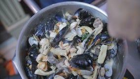 Chef-kok in een keuken het bewegen pot met zeevruchten van oester voor deegwaren stock footage
