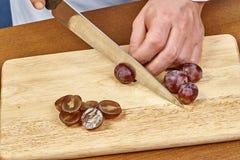 Chef-kok gesneden druiven op een Close-up van de Chef-kok` s handen van de knipselraad Stock Foto