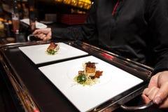 Chef-kok gezet voedsel op dienblad vóór gediend door kelner Royalty-vrije Stock Afbeelding