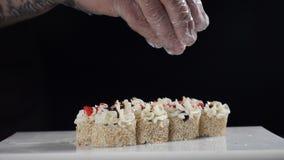 Chef-kok gietend broodje met sesam Sesam die op een sushibroodje vallen - langzaam motieschot De sushi plateren dicht omhoog HD stock videobeelden