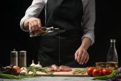 Chef-kok gietende olijfolie, drie verse ruwe lapjes vlees met vlees op een donkere achtergrond Water gevend met olie alvorens, op stock afbeelding