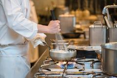 Chef-kok het koken in de keuken stock afbeelding