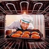 Chef-kok het koken in de oven royalty-vrije stock afbeeldingen