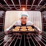 Chef-kok het koken in de oven stock fotografie