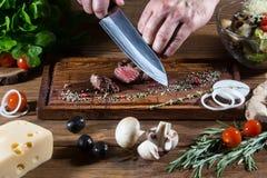 Chef-kok het koken lapje vleesclose-up Royalty-vrije Stock Afbeeldingen