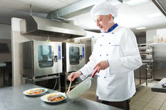 Chef-kok het koken in zijn keuken Stock Foto's