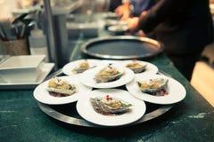 Chef-kok in hotel of restaurantkeuken die en voedsel voor diner koken verfraaien Royalty-vrije Stock Foto's